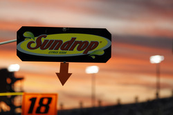 Pit board signs are backlit by sunset
